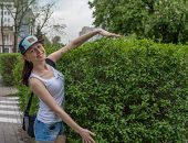 stock photo of stroll  - strolling girl in blue cap with green nature on background - JPG