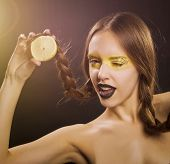 stock photo of eye-wink  - girl holding a lemon in her right hand and winking eye - JPG