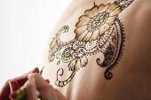 picture of mehndi  - Mehndi. Beautiful henna patterns in process of applying on model
