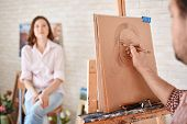 stock photo of muse  - Hand of male artist drawing his muse - JPG