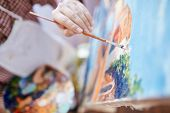 pic of canvas  - Hand of artist with paintbrush painting on canvas - JPG