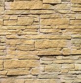 stock photo of tile cladding  - Yellow cladding tiles imitating stones in sunny day - JPG