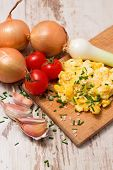 pic of scrambled eggs  - Vertical photo of scrambled eggs with chive with various vegetable around as garlic tomatoes onions plus salt spilled around - JPG