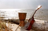 foto of ukulele  - Ukulele & ethnic drum on a beach on a sea and sky background. ** Note: Visible grain at 100%, best at smaller sizes - JPG