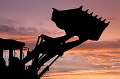 stock photo of risen  - silhouette of risen loader excavator scoop shovel over scenic dawn - JPG