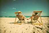 image of couple sitting beach  - Couple sitting in beach chairs and holding hands on a tropical beach   - JPG