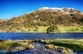 stock photo of scars  - Snow capped Nab Scar and Rydal Water in the English Lake District on a sunny day - JPG