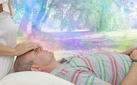 stock photo of senses  - Healing practitioner sensing energy of male client lying supine on couch with a colorful fantasy rainbow bokeh background - JPG