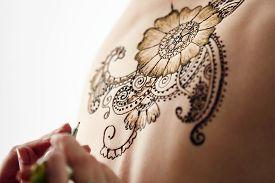 image of mehndi  - Mehndi. Beautiful henna patterns in process of applying on model