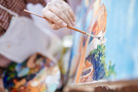 stock photo of canvas  - Hand of artist with paintbrush painting on canvas - JPG