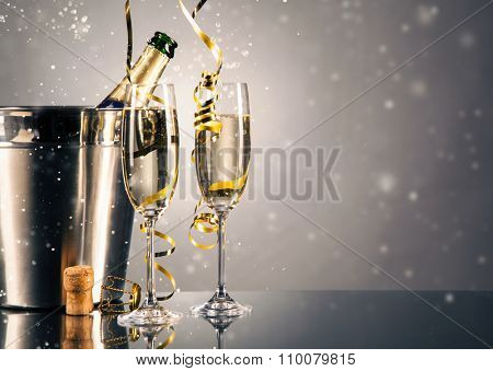 Pair glass of champagne with bottle in metal container. New Year celebration theme with blur spots o