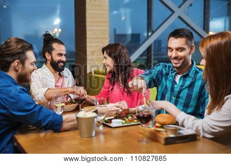 leisure, eating, food, people and holidays concept - smiling friends having dinner and tasting each