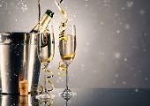 Pair glass of champagne with bottle in metal container. New Year celebration theme with blur spots o poster