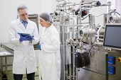 Scientists using tablet to control vats in the lab poster