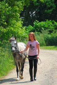 image of horse girl  - young girl walking with a pony on a farm road - JPG