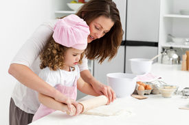 stock photo of mother child  - Mother and daughter using a rolling pin together in the kitchen - JPG