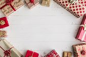 Wrapped Christmas gifts on a white wooden background, overhead shot poster