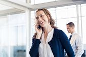 Mature business woman talking over phone in boardroom. Happy businesswoman talking on mobile phone i poster