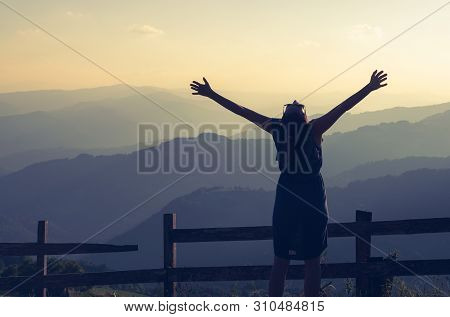 poster of Woman on vacation relaxing in mountain. Summer vacation. Young woman traveler in vacation in nature. Traveler in vacation with backpack in nature. Girl traveler with hands outstretched in vacation. Traveler. Vacation . Backpack. Woman. Nature. Healthy lif