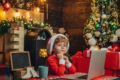Christmas Shopping Concept. Little Genius. Santa Little Helper. Boy Child With Laptop Near Christmas poster