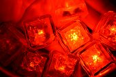 Plastic Glowing Bright Red Ice Cubes In Water. Red Ice Floes Are Floating In A Stainless Steel Dippe poster