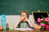 Cute Boy At Lunch Time In Classroom. Young Schoolboy Sitting At Table With Apple In Class Room. Litt poster