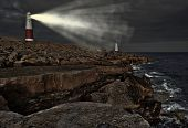 stock photo of promontory  - Old lighthouse with warning light on at night on promontory of rocks facing the ocean - JPG