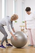 Senior Woman And Middle Age Physiotherapist With Gymnastic Ball poster
