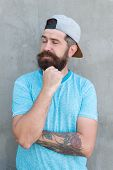 His Beard Is Still In Fashion. Hipster Touching Thick Beard On Grey Wall. Bearded Man In Fashion Hip poster