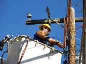 foto of lineman  - Male Power Worker in a Lift Bucket Truck Working on Power Lines - JPG