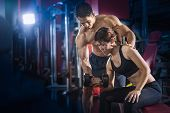Young Woman Exercise In A Gym With The Help Of Her Personal Trainer, Fitness Instructor Exercising W poster