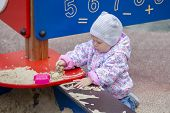 Baby Girl Playing With Sand. A Girl In A Pink Jacket And Hat For A Walk Plays With Sand In A Sandbox poster