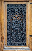Whimsical Ornate Gratings Of Vintage Wooden Door With Framed Door Panel. Closeup Of Antique Ornate M poster