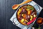 Jamaican Curry Goat - Slow Cooked Jamaican Spiced Meat And Veggies Curry In A Pot On A Black Wooden  poster