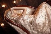 Elegant Blond Woman In Beige Dress Posing On Luxury Sofa In Royal Interior. Fashion Beautiful Sensua poster
