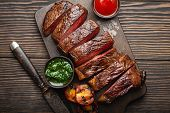 Grilled Or Fried And Sliced Marbled Meat Steak With Fork, Tomatoes As A Side Dish And Different Sauc poster