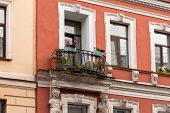 Elegant Balcony With Flowers On An Old Building With Two Female Statues Of Caryatids poster