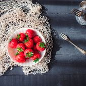 Freshly Picked Juicy Organic Strawberries In Ceramic Bowl On Rustic Black Wooden Kitchen Table Light poster