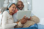 Front view of diverse senior couple using a digital tablet on sofa in beach house. Authentic Senior  poster