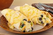 picture of enchiladas  - Two chicken enchiladas with melted cheese on a plate - JPG