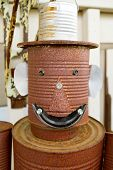 pic of tin man  - A tin man is made out of old rusty cans and he is smiling at the camera - JPG