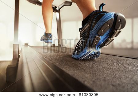 Man running in a gym on a treadmill concept for exercising, fitness and healthy lifestyle poster