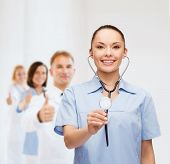 healthcare and medicine concept - smiling female doctor or nurse with stethoscope and team on the ba