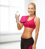 fitness, heatl and diet concept - sporty woman with bottle of water and towel