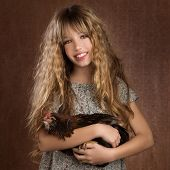 children fashion farmer girl holding hen in retro vintage background