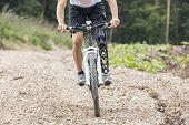 stock photo of prosthesis  - Mountain bike rider with leg prosthesis rides a gravel track - JPG