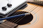 picture of risque  - Notebook and pencil on guitar and book - JPG