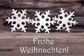 pic of weihnachten  - Three Wooden Snowflakes with the German Words Frohe Weihnachten which means Merry Christmas - JPG