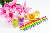 pic of diffusion  - Studio shot of bottles of scented oil multi colored reed diffuser and pink flowers - JPG