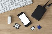 picture of memory stick  - An USB Stick an external hdd different memory cards a modern keyboard and a smartphone with white isolated screen on a wooden desk - JPG